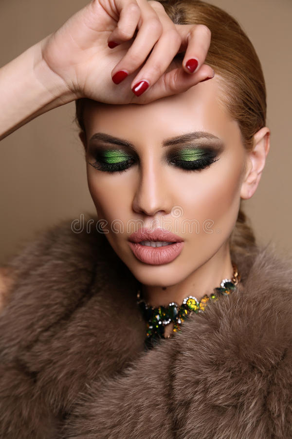 Mulher com cabelo louro e composição brilhante, no casaco de pele elegante com joia fotos de stock royalty free