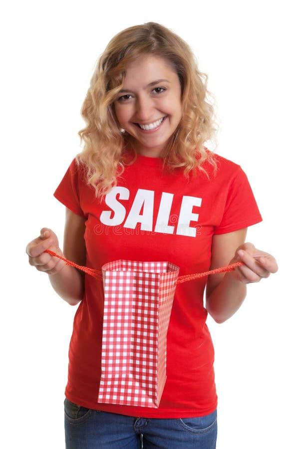 Mulher com cabelo louro em uma venda-camisa que guarda um saco de compras imagens de stock