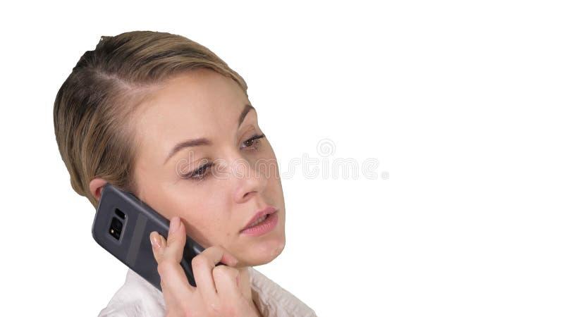 Mulher com cabelo louro que fala no telefone celular no fundo branco imagem de stock