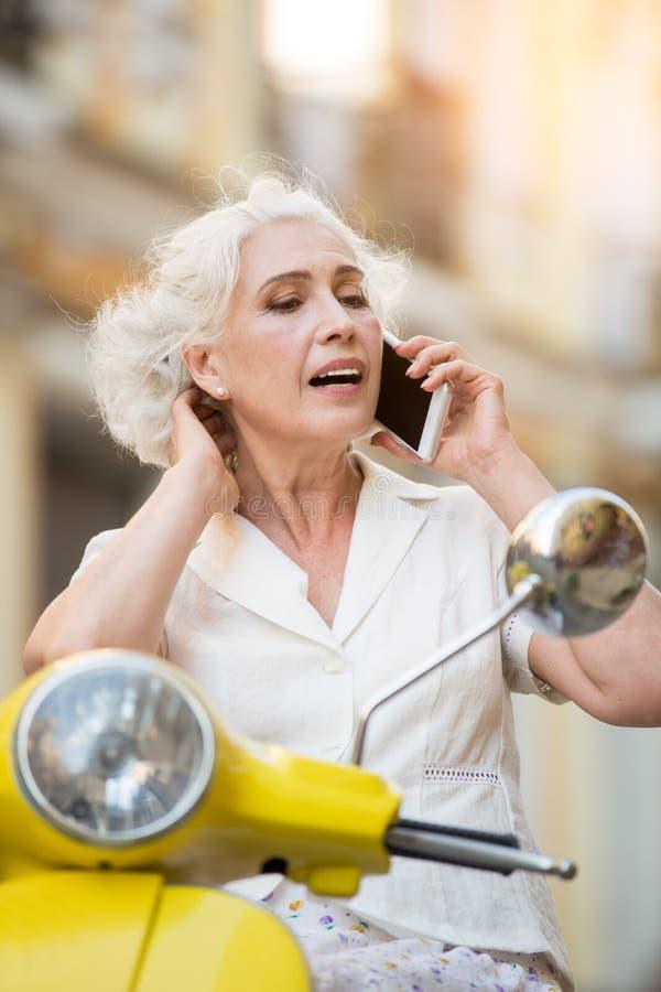 Mulher com cabelo tocante do telefone fotografia de stock royalty free
