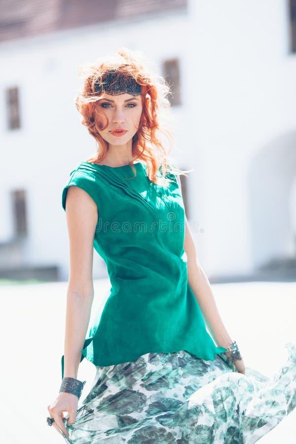 Mulher com cabelo vermelho e o vestido verde fotografia de stock