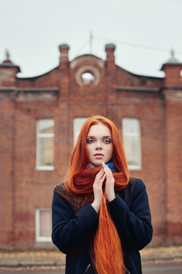 A mulher com cabelo vermelho longo anda no outono na rua Olhar sonhador misterioso e a imagem da menina Passeio da mulher do ruiv foto de stock royalty free