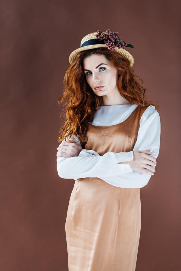 Mulher com cabelo vermelho longo no chapéu bege do vestido e de palha imagens de stock