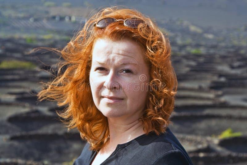 Mulher com cabelo vermelho na paisagem vulcânica fotografia de stock royalty free