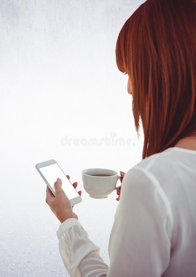 Mulher com café e telefone contra a parede branca fotos de stock royalty free