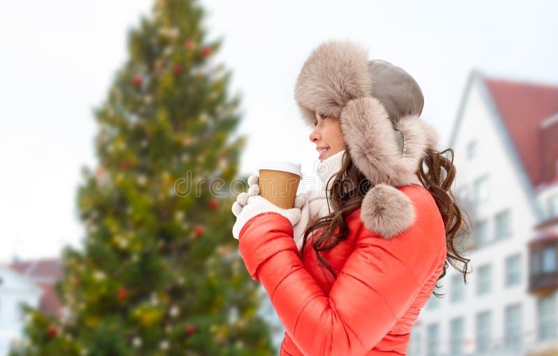 Mulher com café sobre a árvore de Natal em tallinn foto de stock