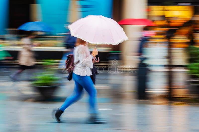 Mulher com caminhadas do guarda-chuva na cidade chuvosa no borrão de movimento fotos de stock royalty free