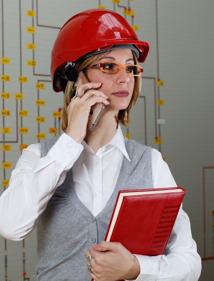 A mulher com capacete vermelho faz a chamada no centro de controle da distribuição de poder imagens de stock royalty free