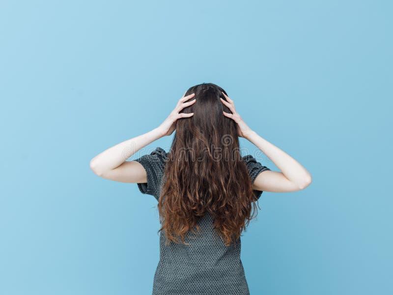Mulher com a cara coberta atrás de seu cabelo foto de stock