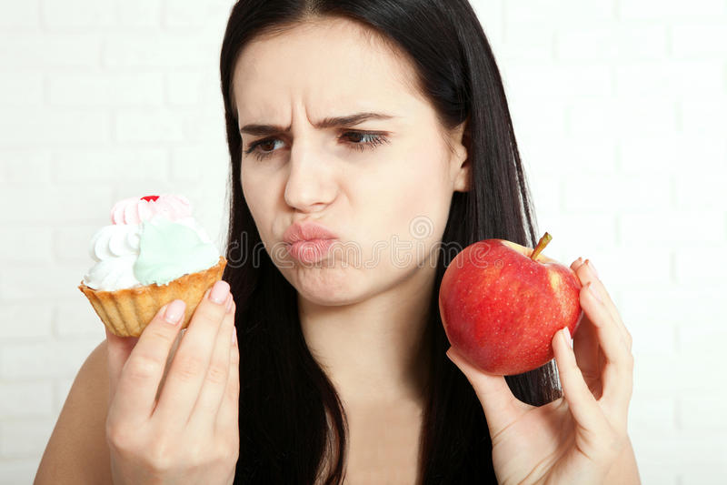 Mulher com a cara do close up da maçã As mulheres bonitas existem para limpar a pele na cara que escolhe comer uma maçã ou endure fotos de stock