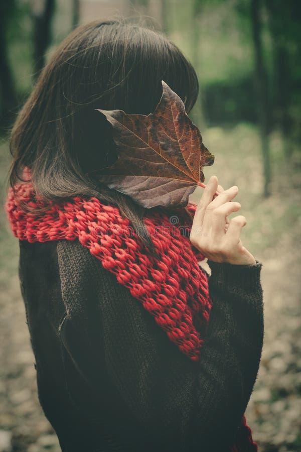 Mulher com a cara do couro cru da folha do outono exterior foto de stock