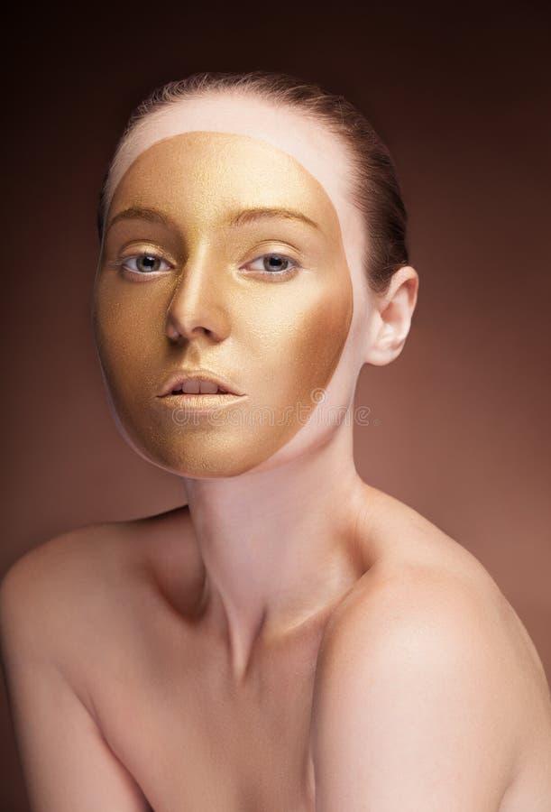 A mulher com cara do ouro compõe a forma no marrom fotos de stock