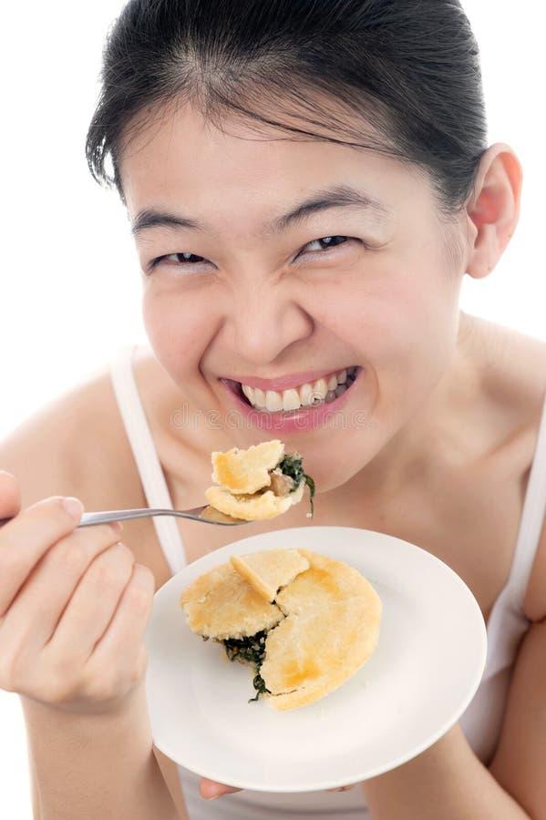 Mulher com cara do sorriso que come a torta fotos de stock royalty free