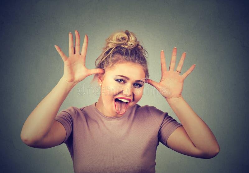 Mulher com a cara engraçada que zomba alguém que ridiculariza algo em uma maneira cruel fotografia de stock royalty free