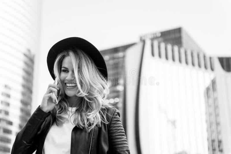 A mulher com a cara feliz no chapéu à moda fala no telefone imagens de stock