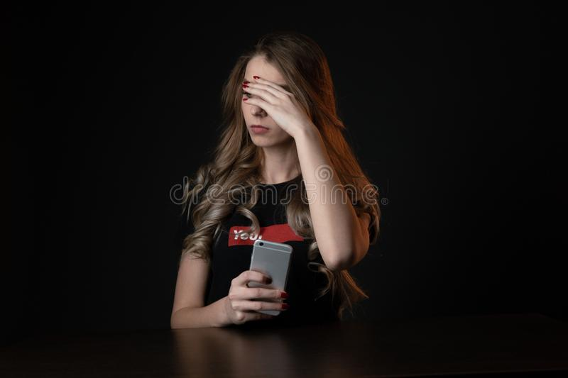 Mulher com a cara surpreendida negativa que olha algo no smartphone Adolescente triste com o telefone celular, assustado de imagem de stock