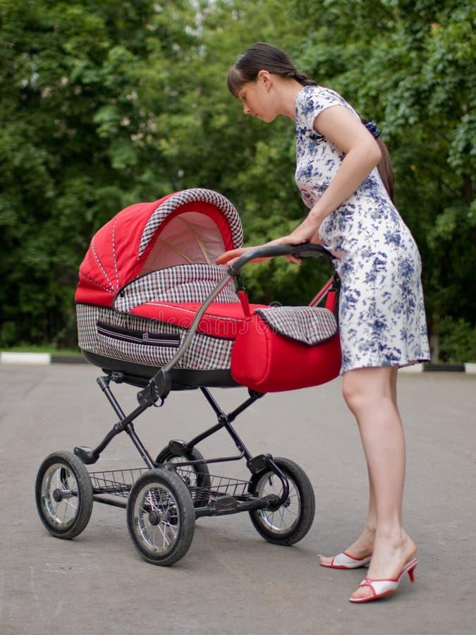 Mulher com carro de bebê foto de stock royalty free