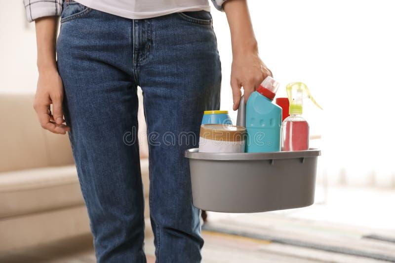 Mulher com a cesta de produtos de limpeza profissionais dentro fotos de stock