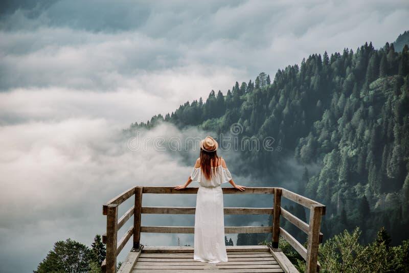 A mulher com chapéu e posição branca do vestido contra montanhas na natureza imagem de stock royalty free
