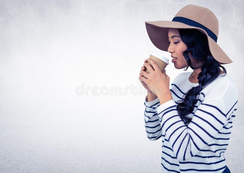 Mulher com chapéu que bebe do copo de café contra a parede branca fotografia de stock royalty free