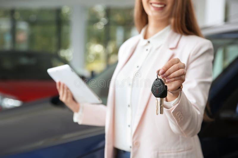 Mulher com chaves da tabuleta e do carro no automóvel moderno imagem de stock royalty free