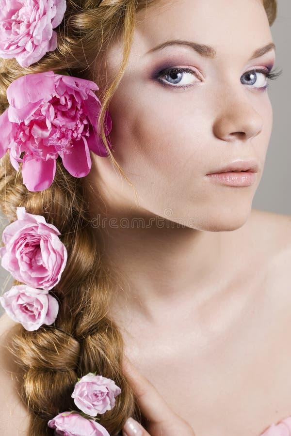 Mulher com com as tranças e as rosas no cabelo foto de stock