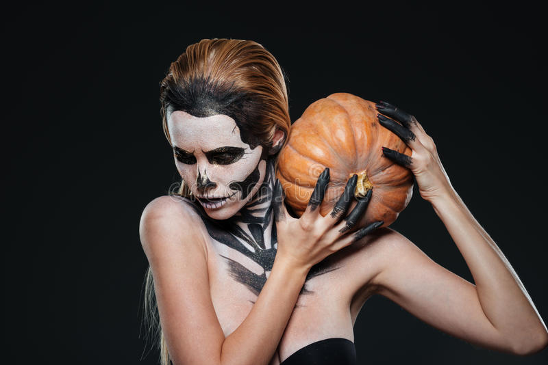 Mulher com a composição assustado do Dia das Bruxas que guarda a abóbora imagens de stock royalty free