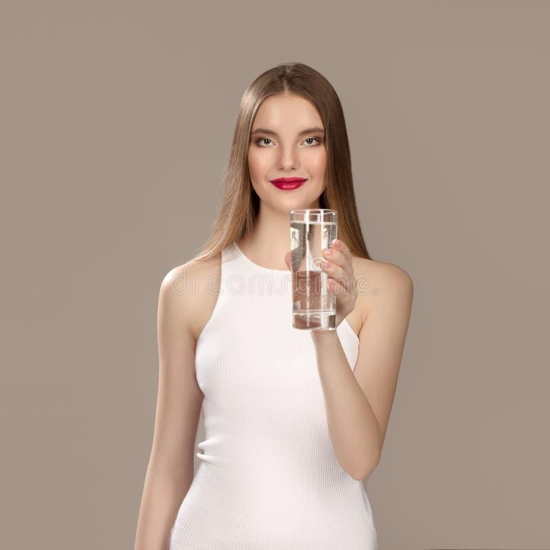 Mulher com composição brilhante em um vestido branco bonito Água mineral de sorriso da menina fotografia de stock