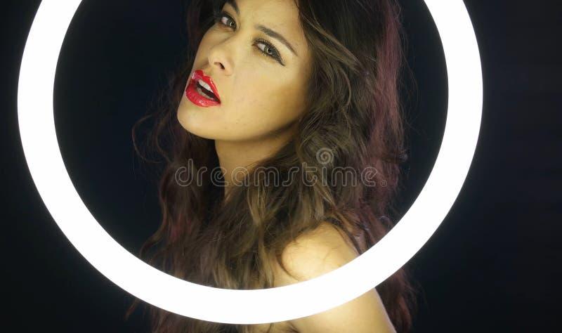 Mulher com composição desarrumado atrás do círculo fluorescente foto de stock royalty free