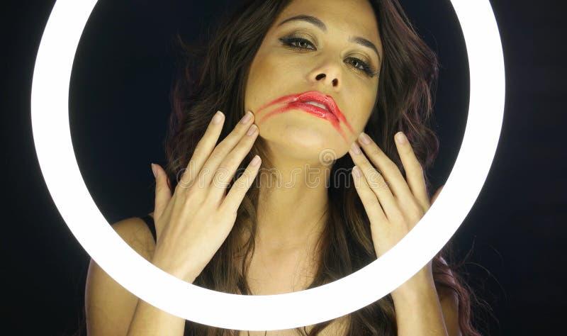 Mulher com composição desarrumado atrás do círculo fluorescente imagem de stock