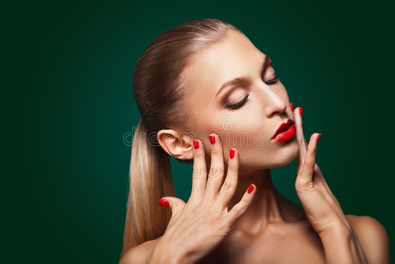 Mulher com composição vermelha e tratamento de mãos sobre o verde imagens de stock