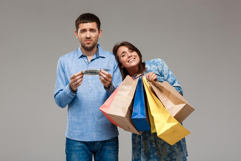 Mulher com compras, homem que guarda o último dinheiro sobre o fundo cinzento fotos de stock royalty free
