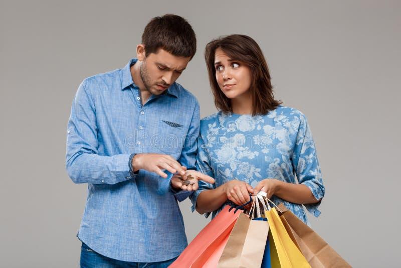 Mulher com compras, homem que guarda o último dinheiro sobre o fundo cinzento fotografia de stock royalty free