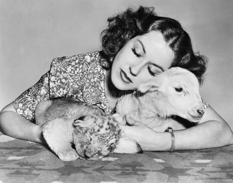 Mulher com cordeiro do sono e filhote de leão (todas as pessoas descritas não são umas vivas mais longo e nenhuma propriedade exi fotografia de stock