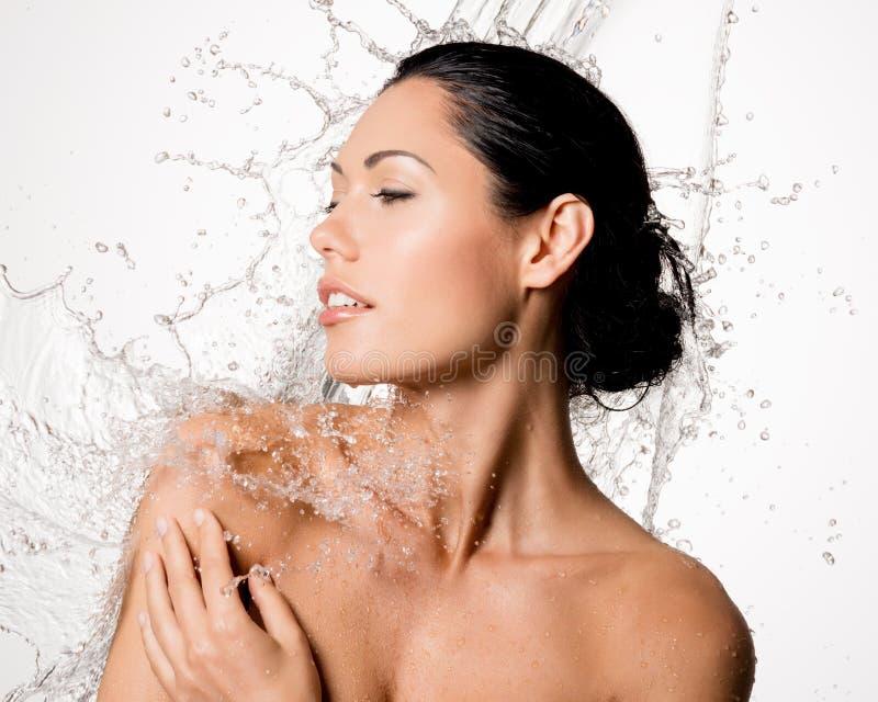 A mulher com corpo molhado e espirra da água imagem de stock