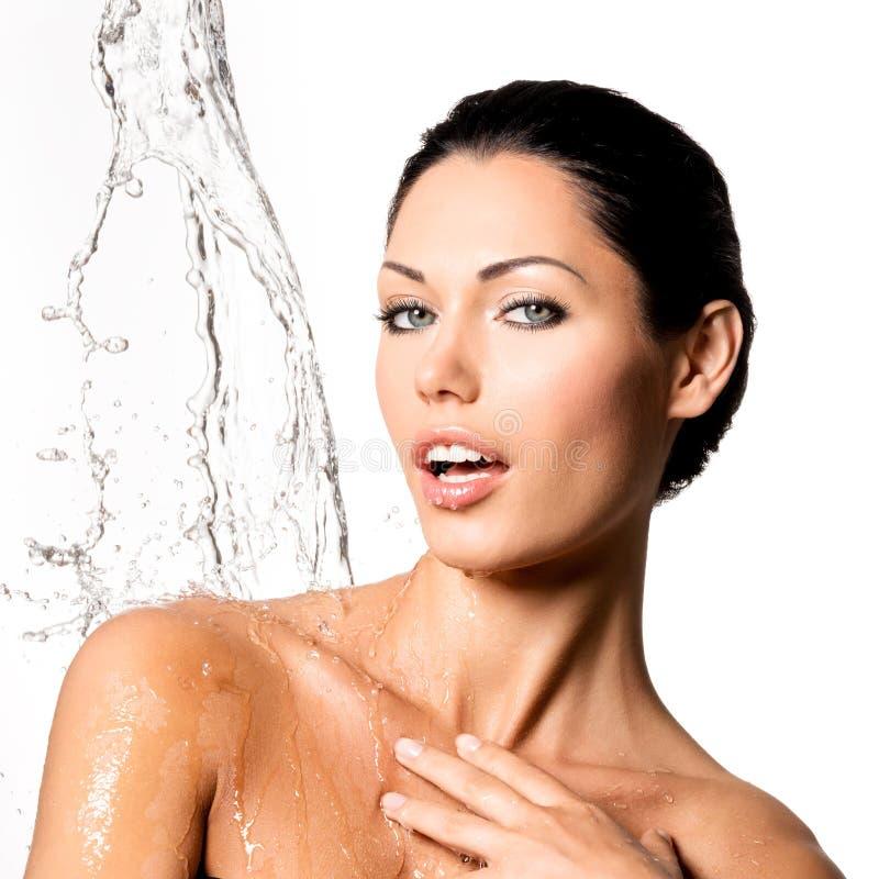 A mulher com corpo molhado e espirra da água fotos de stock