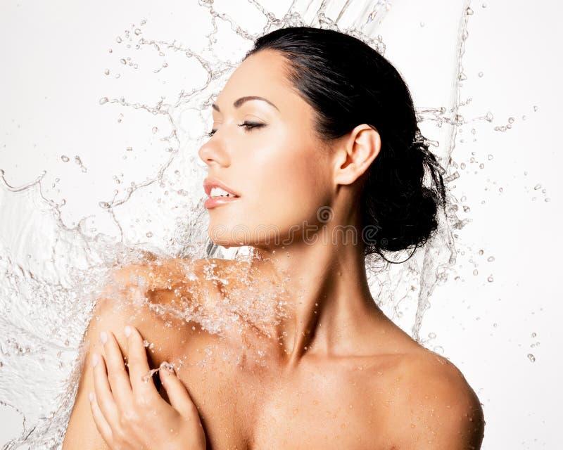 A mulher com corpo molhado e espirra da água imagens de stock