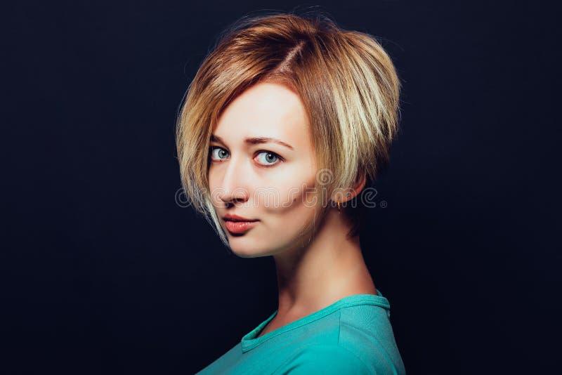 Mulher com corte de cabelo curto em um fundo escuro fotografia de stock royalty free