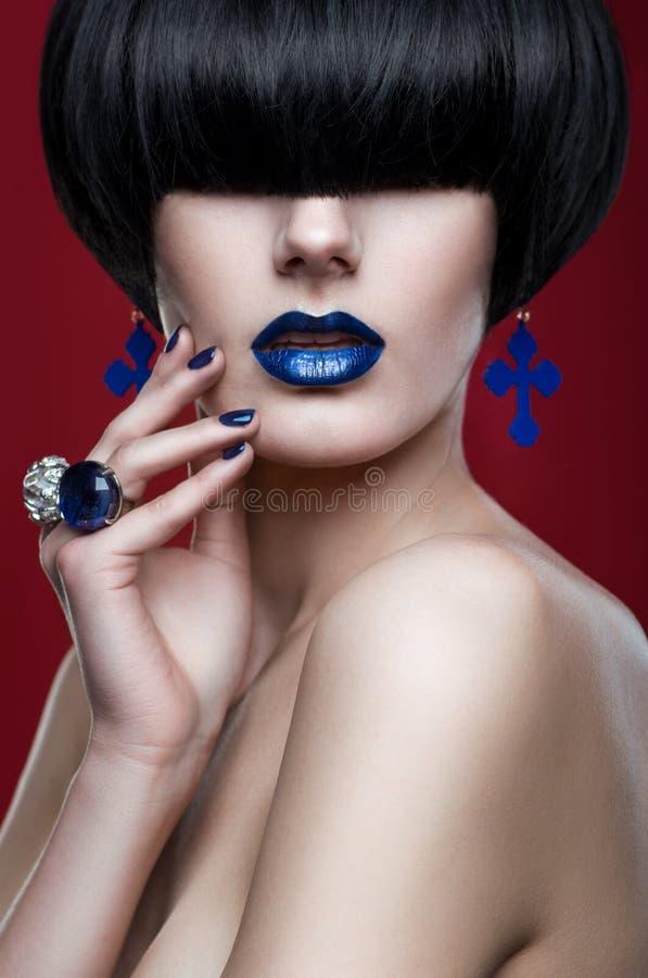 Mulher com corte de cabelo moderno com bordos azuis imagem de stock