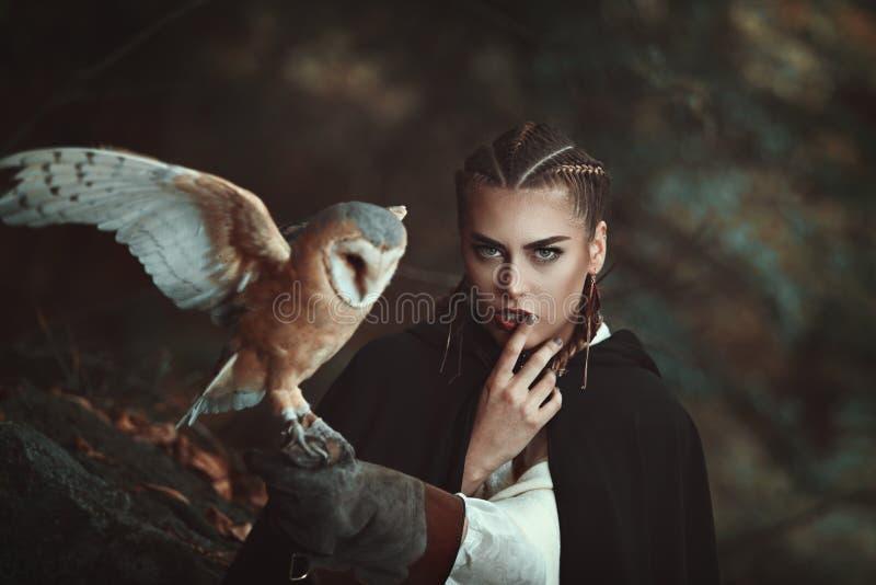 Mulher com a coruja de celeiro em seu braço fotos de stock royalty free
