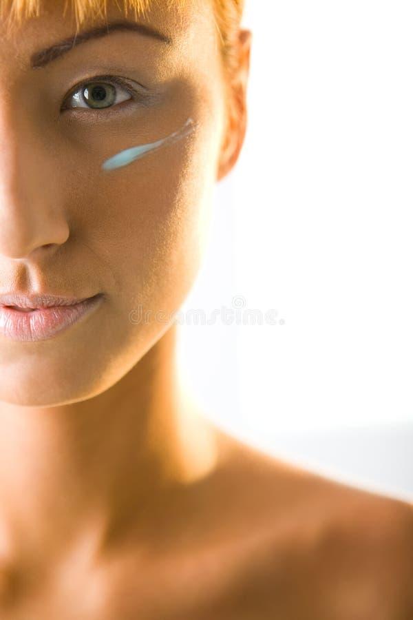 Mulher com creme na face imagens de stock