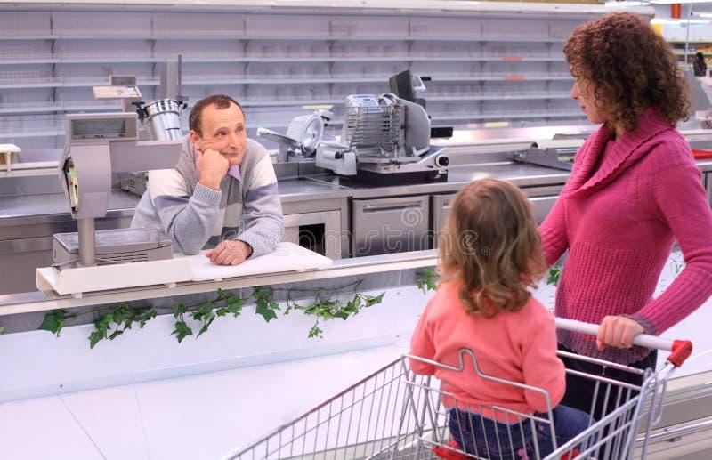 Mulher com criança e o vendedor furado na loja imagens de stock royalty free