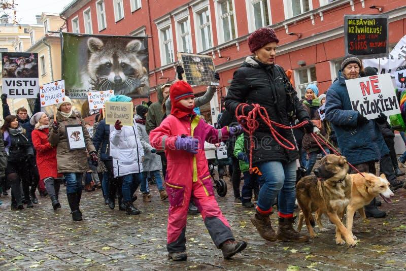 Mulher com a criança e os dois cães, participando 'em março para animais em Riga, Letónia imagem de stock royalty free