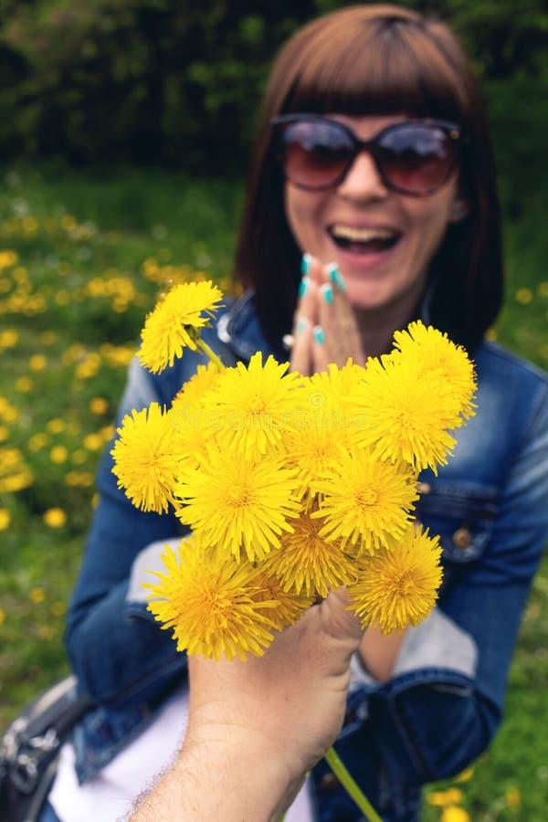 Mulher com dentes-de-leão em um parque verde da mola fora Fêmea nova com dentes-de-leão amarelos foto de stock royalty free