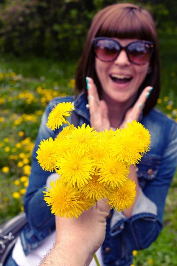 Mulher com dentes-de-le?o em um parque verde da mola fora F?mea nova com dentes-de-le?o amarelos foto de stock
