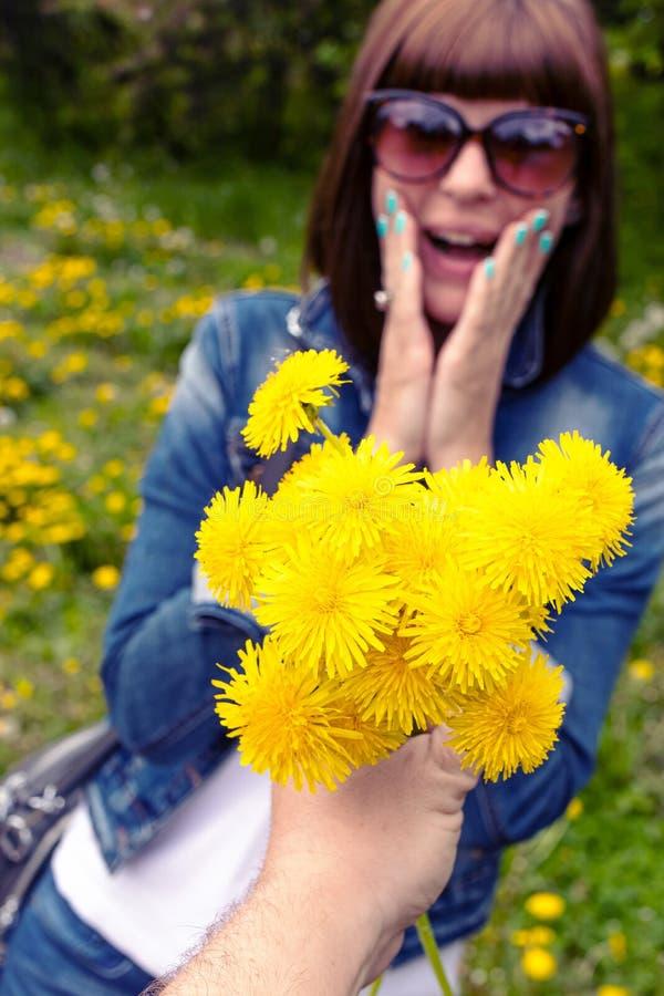 Mulher com dentes-de-le?o em um parque verde da mola fora F?mea nova com dentes-de-le?o amarelos fotografia de stock