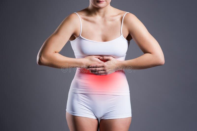 Mulher com dor abdominal, dor de estômago no fundo cinzento imagem de stock royalty free
