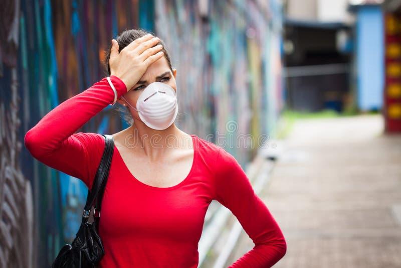 Mulher com a dor de cabeça que veste uma máscara protetora imagens de stock royalty free
