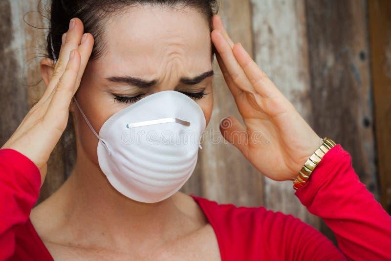 Mulher com a dor de cabeça que veste uma máscara protetora fotos de stock royalty free