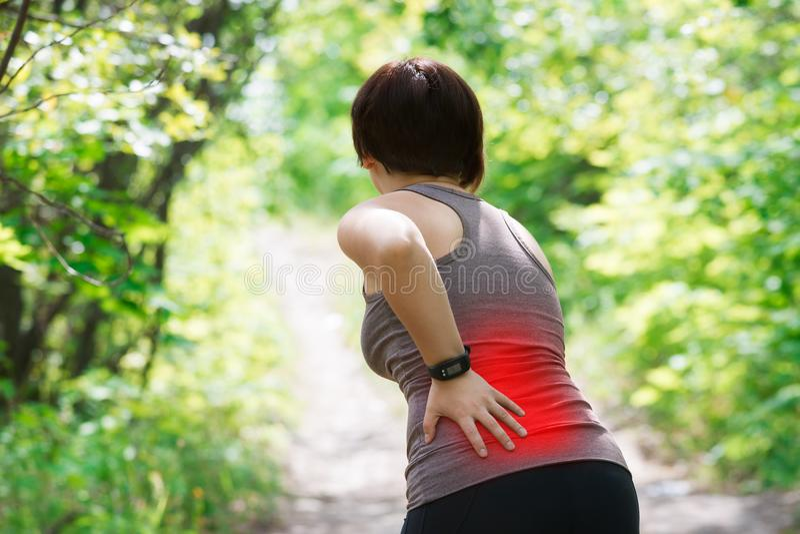 Mulher com dor nas costas, inflamação do rim, ferimento durante o exercício imagens de stock